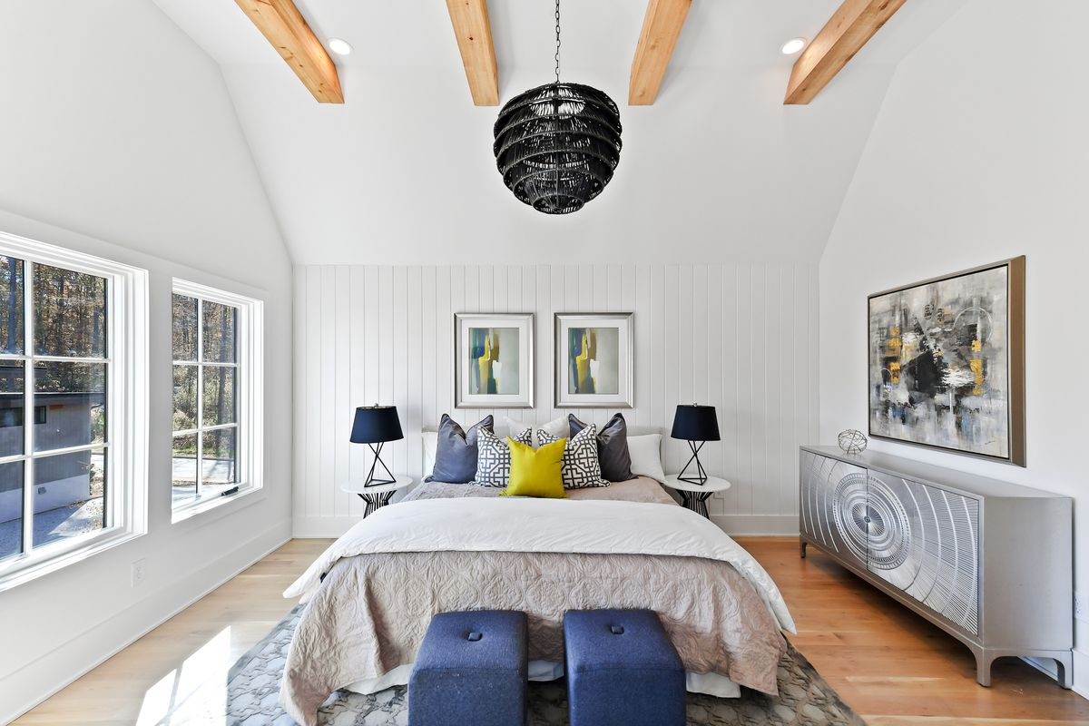 Large bedroom with high, wood beam ceiling, bed, nightstands with lamps, silver dresser, two blue ottomans and area rug.