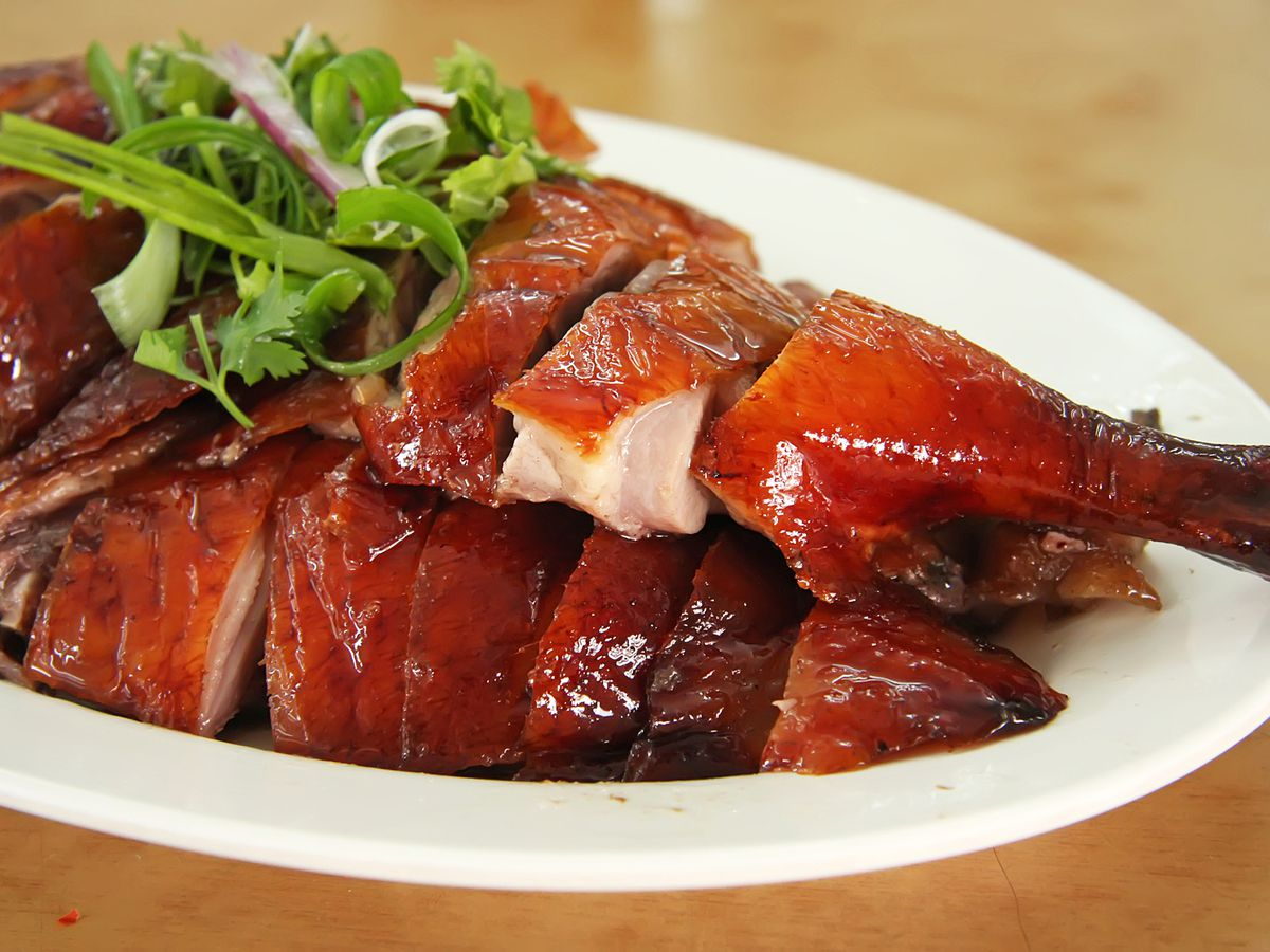 A plate with a whole, sliced crispy Chinese roast duck