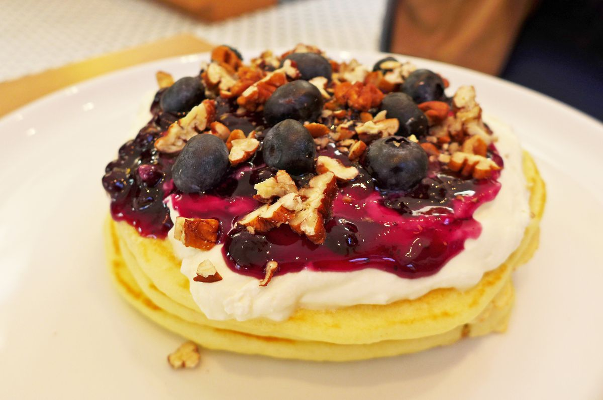 A stack of three normal pancakes with whipped cream, blueberries, and crushed walnuts on top...