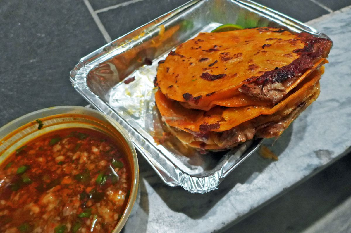 A stack of red mulitas in a rectangular metal container with a plastic container of red soup on the side.