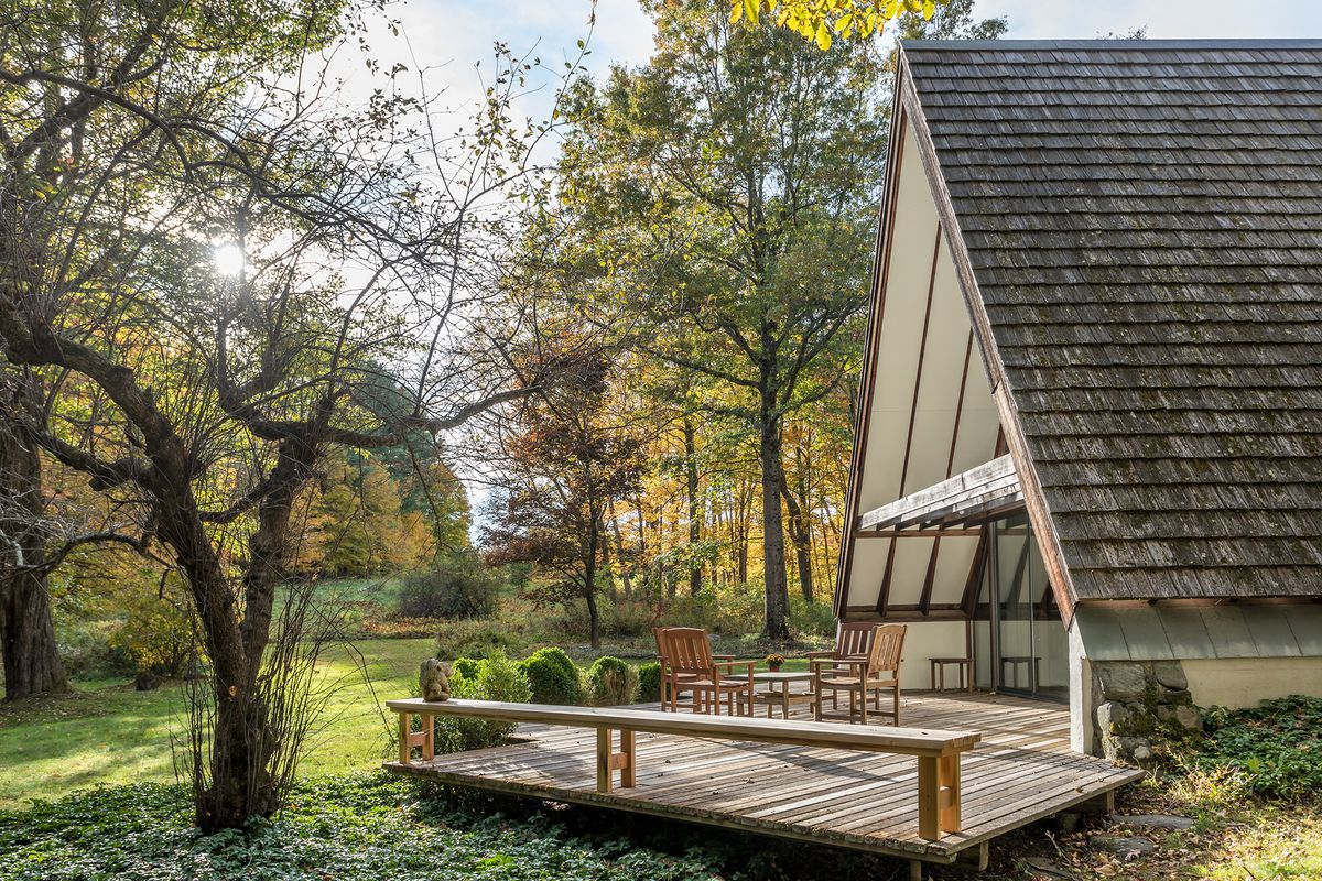 A wooden deck is off of a large A-frame house. There is a wooden dining set on the deck and trees in the yard.
