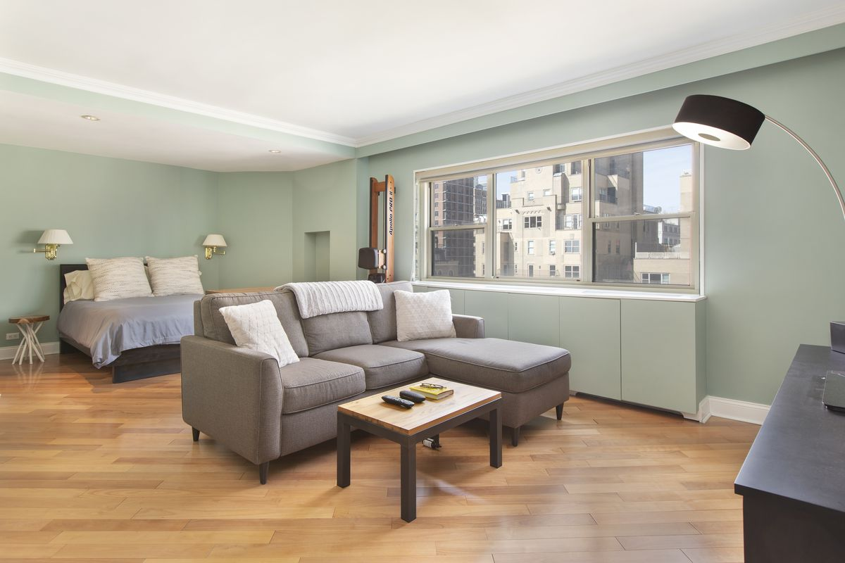 A bedroom with light green walls, hardwood floors, a grey couch, and a bed.
