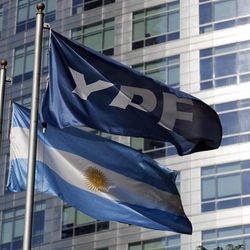 An Argentine flag, bottom, and a flag of the YPF oil company flutter in front of the YPF headquarters in Buenos Aires, Argentina, Monday, April 16, 2012. Argentine President Cristina Fernandez on Monday proposed a bill to expropriate 51 percent of the shares of YPF oil company that is controlled by Spain's Repsol, moving ahead with the plan despite fierce opposition from Madrid.