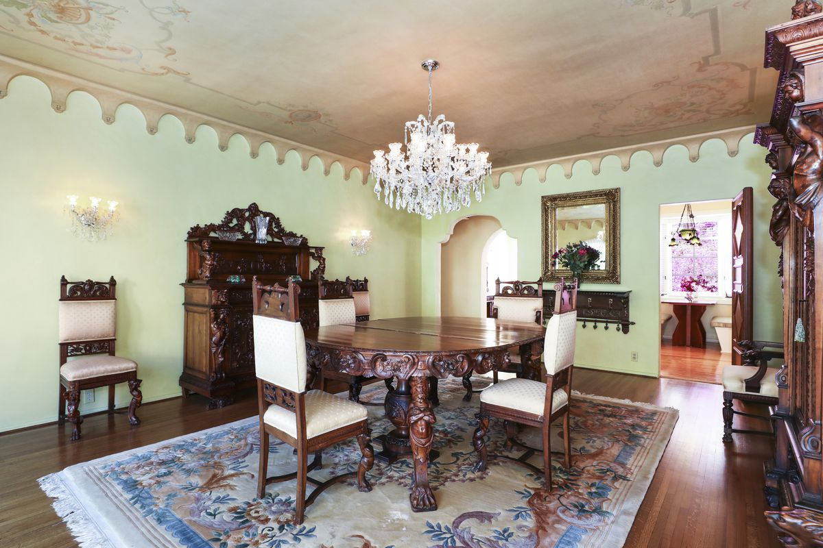 A room with green walls and a chandelier that hangs above a large circular dining table