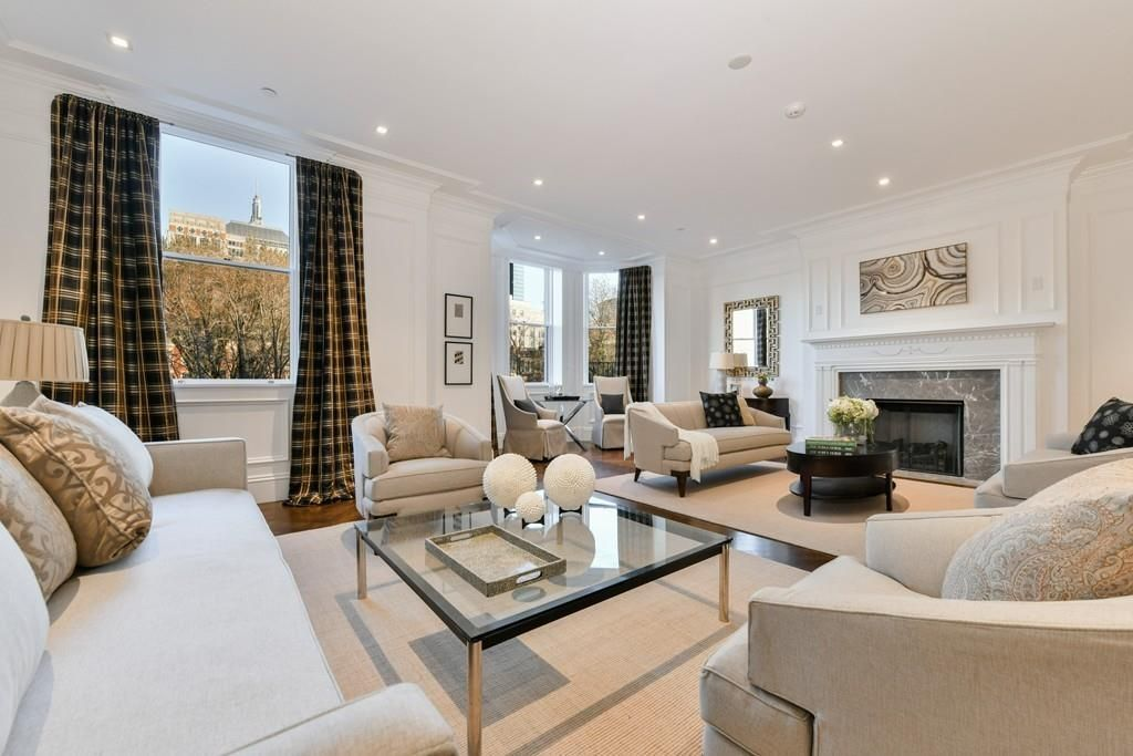 A plush living room with furniture and a fireplace, and a window overlooking a city street.