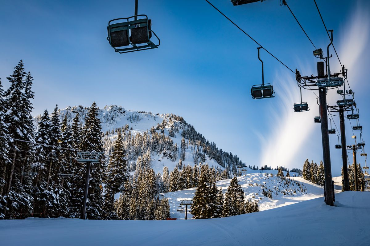 Over a snowy landscape—snow in the foreground, ramping up to an evergreen-and-snow-covered mountain peak in the background—wooden poles support an open ski chair lift.