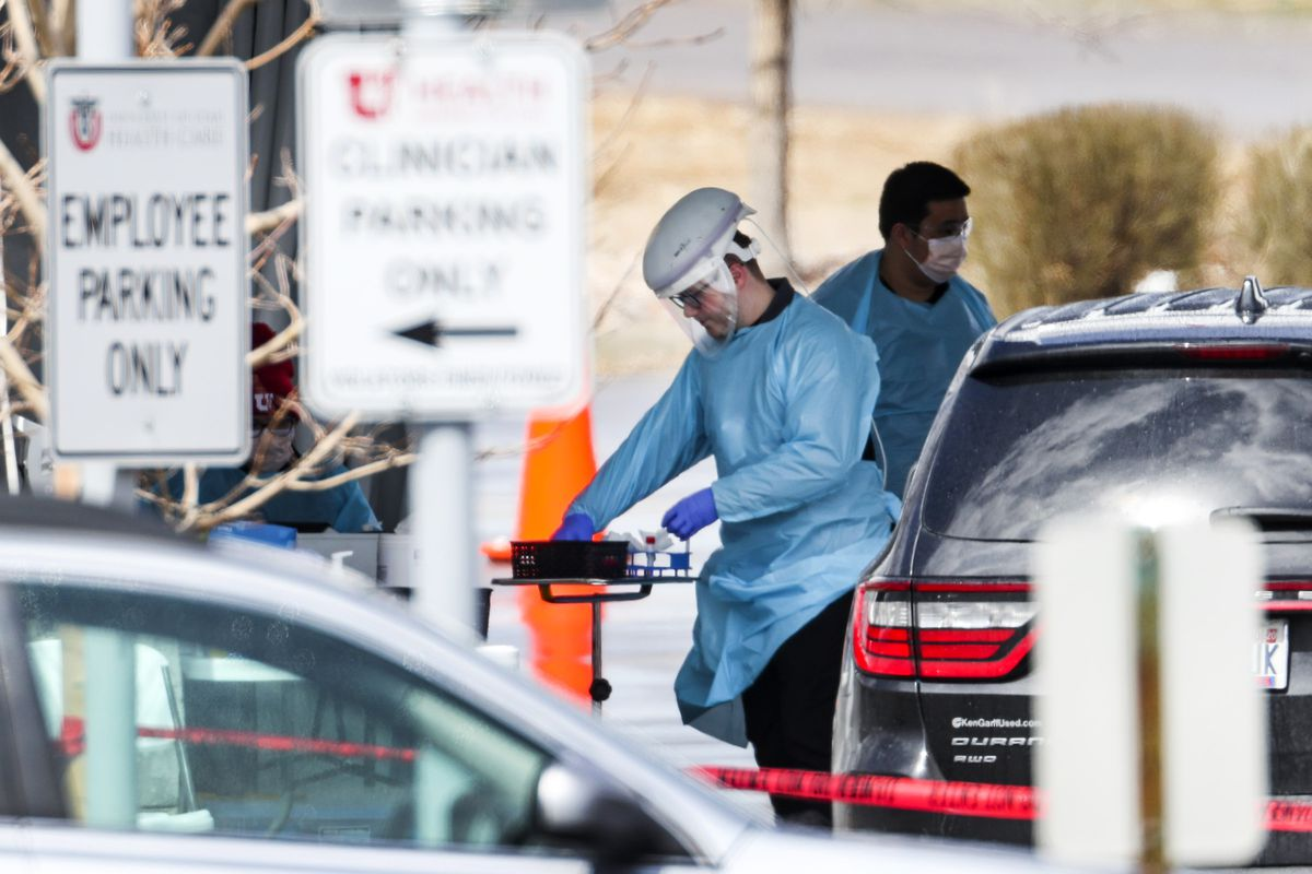 Hospital employees work at a drive-thru COVID-19 testing tent outside University of Utah Health's South Jordan Health Center on Monday, March 30, 2020.