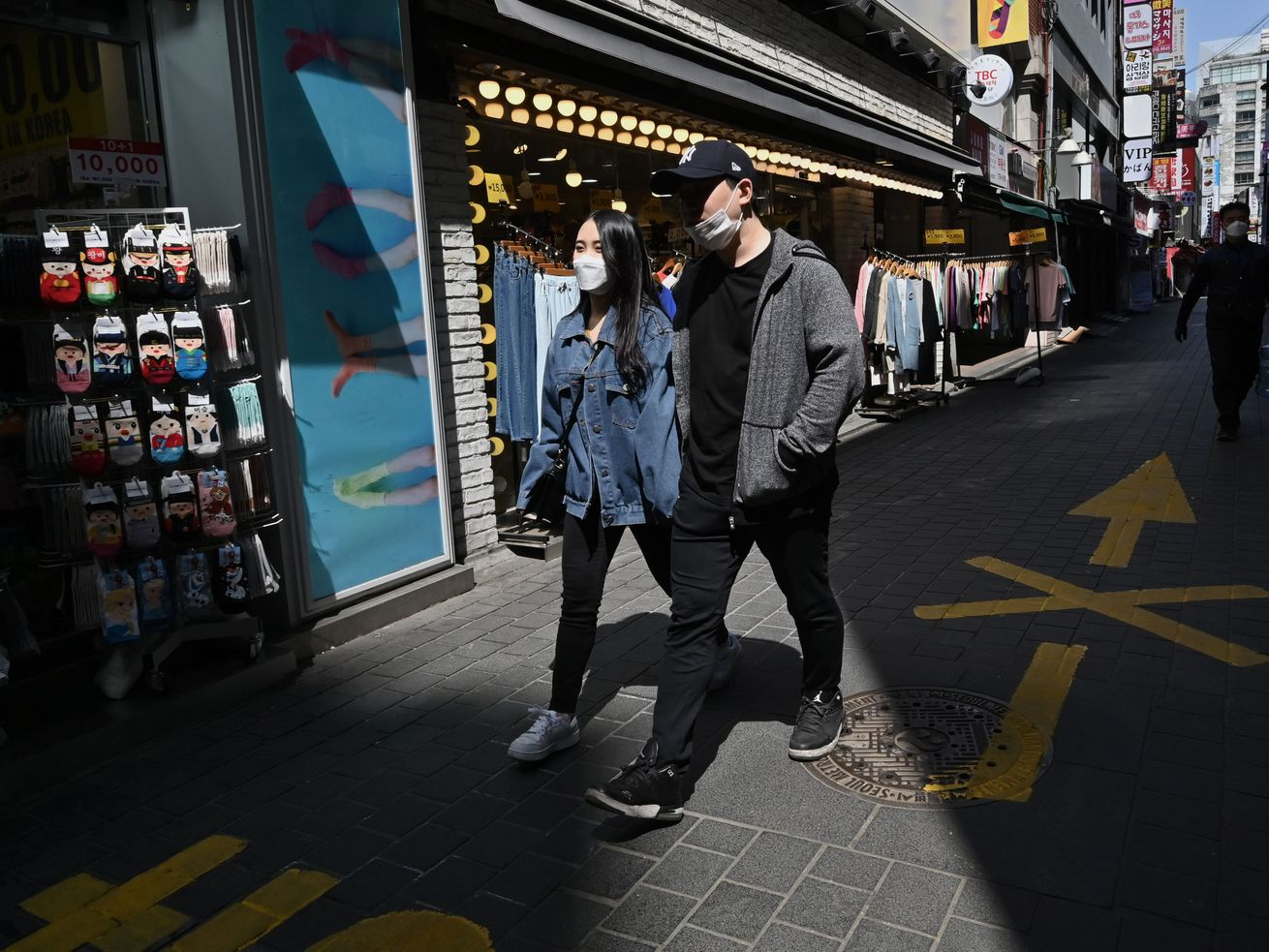 A woman and man hold hands while wearing face masks; they walk out of a shadowed area and into the sunlight.