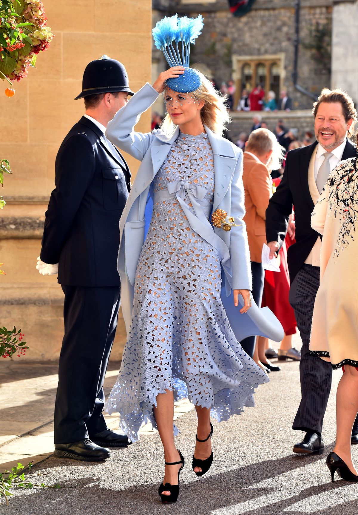 Poppy Delevingne holds a hand to her head to keep her hat in place.
