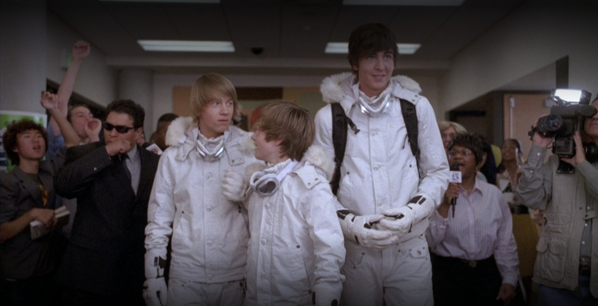 three boys in white snowsuits, looking a bit intimidated as a crowd cheers