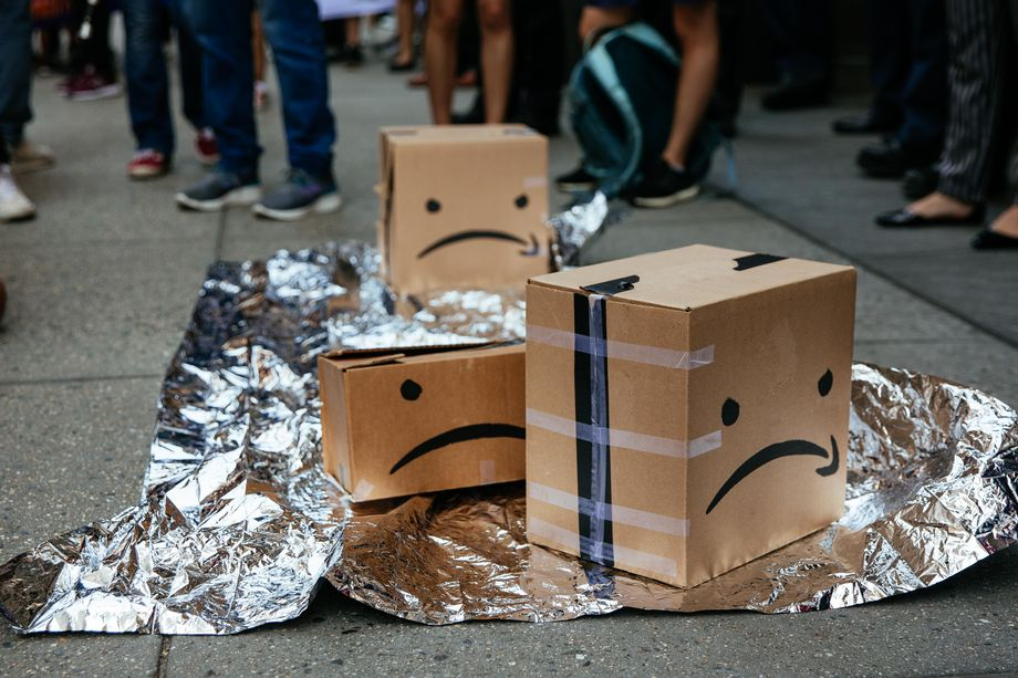 Amazon boxes with drawn-on sad faces (the Amazon logo upside down) sit on the pavement atop a silver groundsheet.