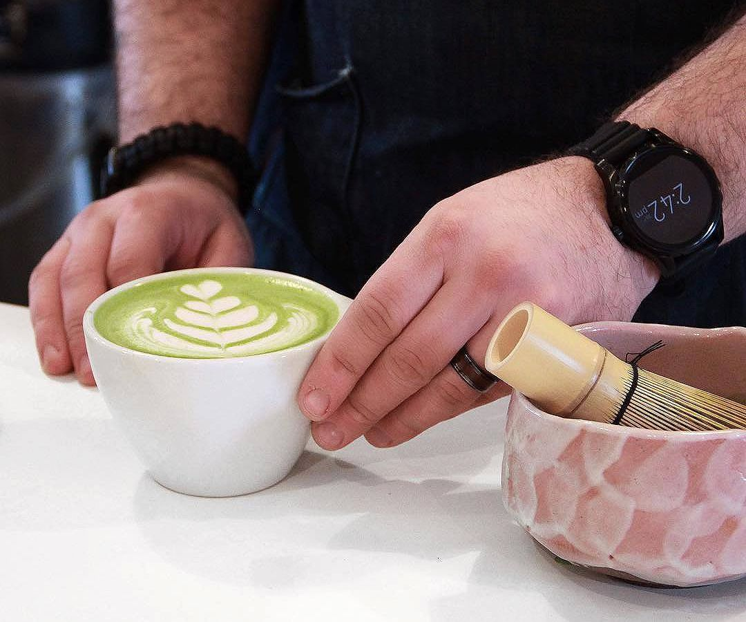A man in a blue jean colored apron holds a green matcha latte in a bistro cup