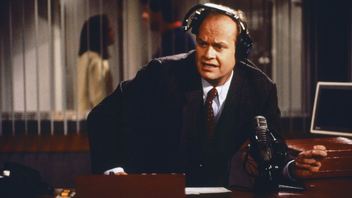 """A still from the NBC show """"Frasier"""" with the titular character inside his radio booth, wearing headphones and looking concerned"""