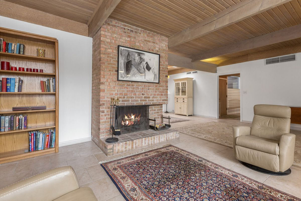 A sitting area next to a hearth with an area rug and wood bookshelves.