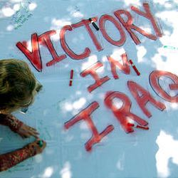 """Roberta Emery of Magna signs """"God Bless"""" on a banner supporting troops in Iraq Tuesday at Salt Palace."""
