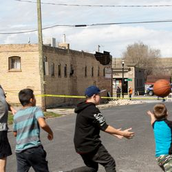 The Bolen family plays basketball with a neighbor outside their Magna home near Colosimo's on Wednesday, March 18, 2020. The Magna establishment was damaged by a 5.7 magnitude earthquake earlier in the day.