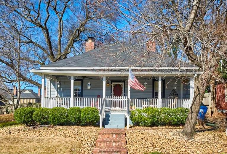 A white and blue home with a large porch and American flag in front.