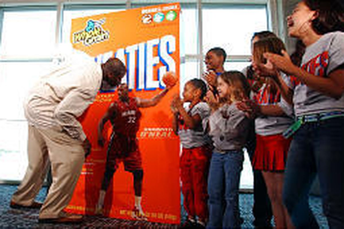 Miami Heat's Shaquille O'Neal kisses the top of his head on a Wheaties cereal box Wednesday in Miami.