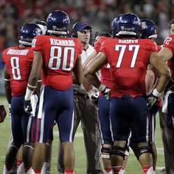 Arizona's head coach Rich Rodriguez, center, talks to his players on the sidelines during a timeout against Oklahoma State the first half of an NCAA college football game at Arizona Stadium in Tucson, Ariz., Saturday, Sept. 8, 2012.