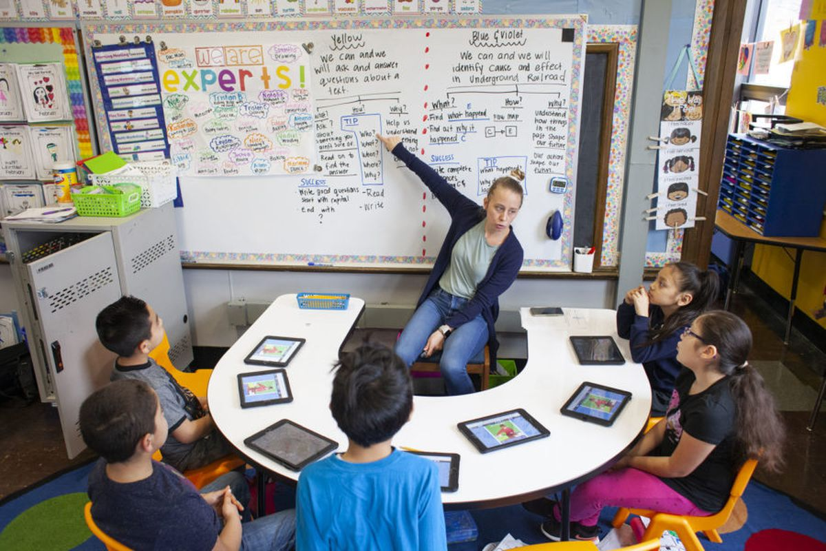 Teacher Kathy McInterney, center, spends intervals of time dedicated to teaching a specific group of students during class at CICS West Belden. The Chicago charter school employs the personalized learning method for its K-8 students.