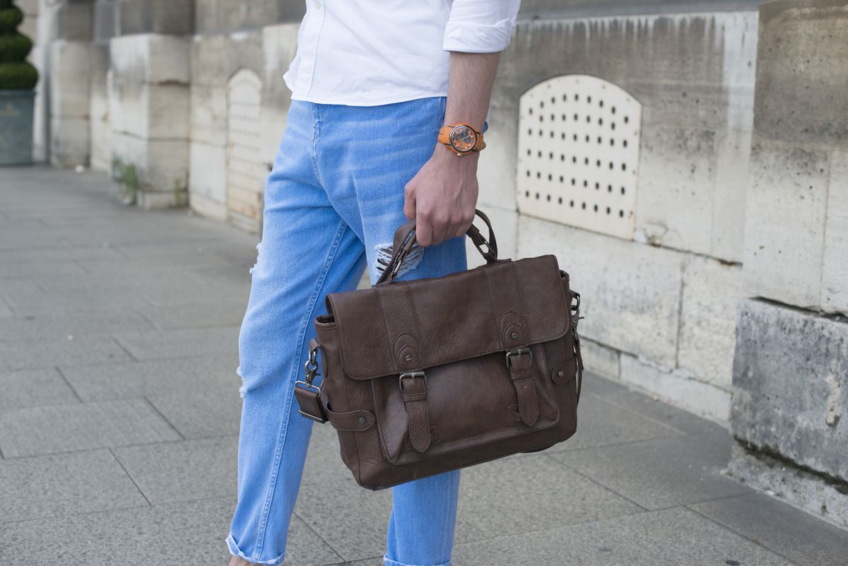 A man in a white shirt and jeans holding a brown saddle bag.