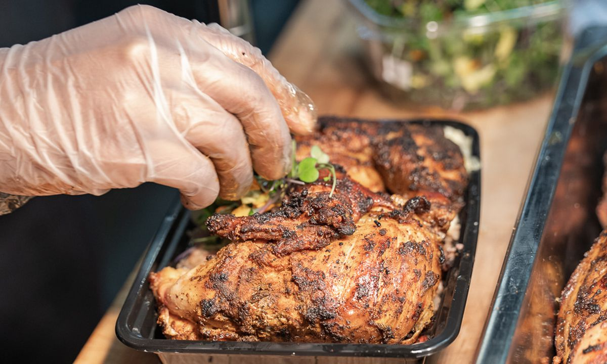 Two gloved hands place small green leaves on a blackened chicken leg