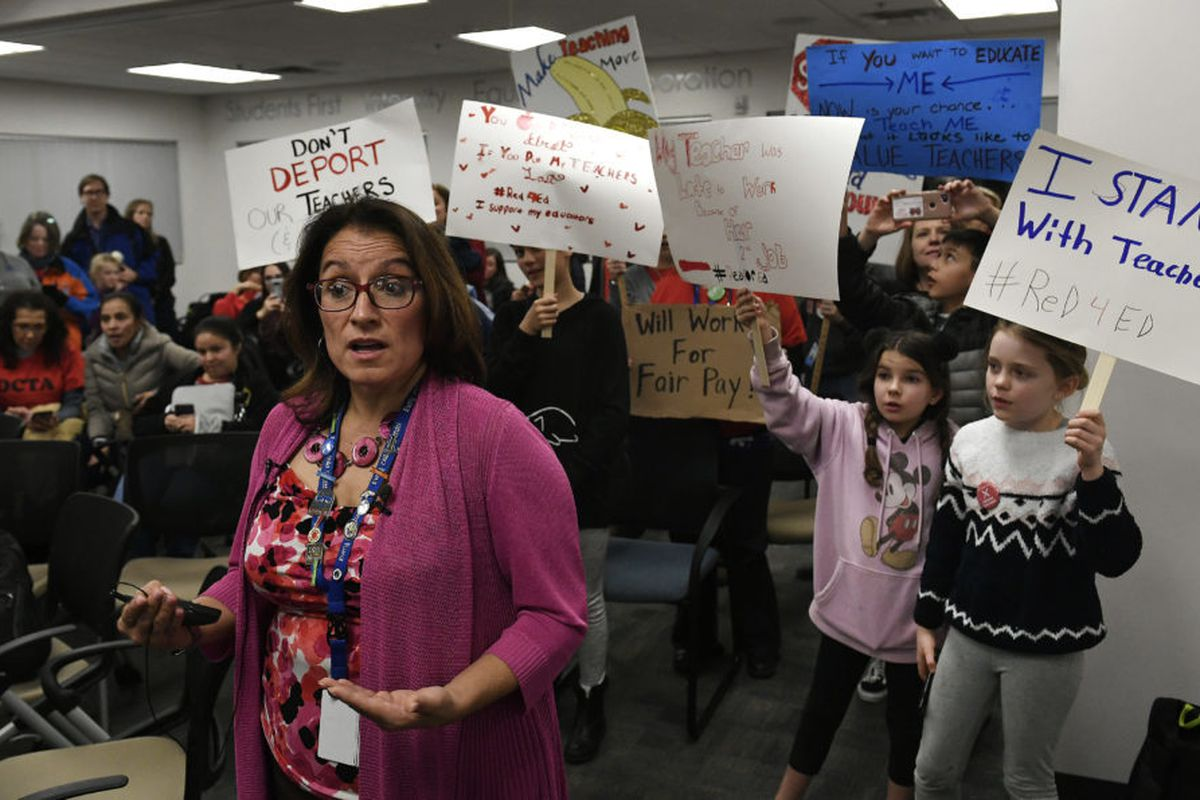 Denver Superintendent Susana Cordova answers questions for the media as students hold up signs behind her after teachers rejected the district's latest proposal.