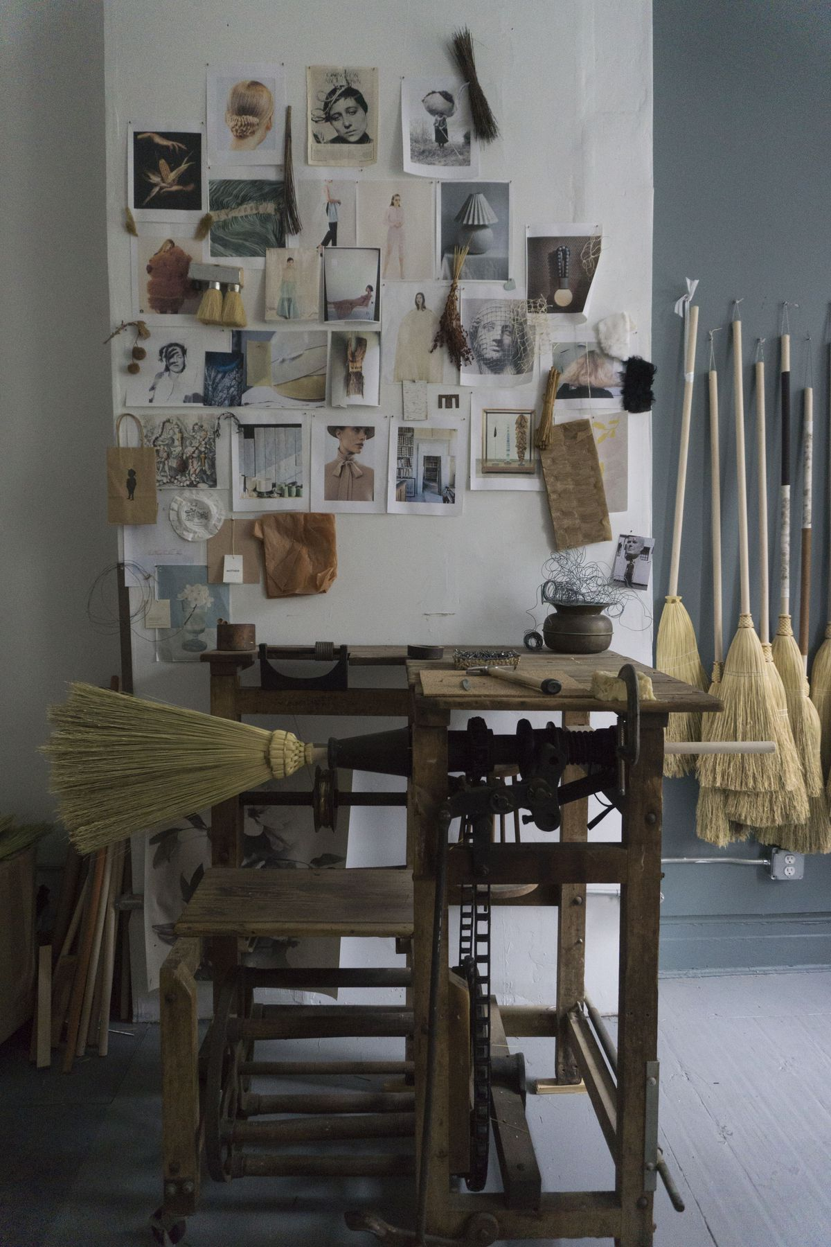 A broom is inserted into a broom-machine in front of a wall of hanging brooms and a mood board.
