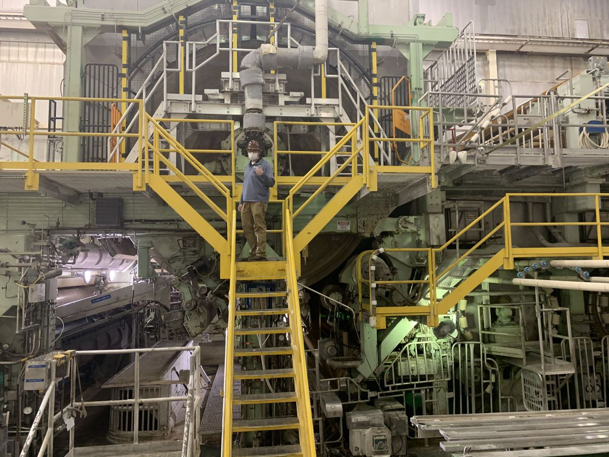 An image of John Patteson standing atop a paper machine.