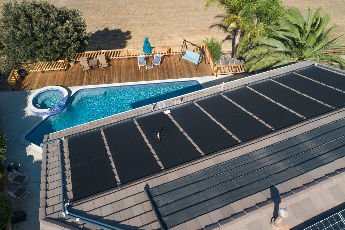 Solar panels on the roof of a home overlooking a pool in the backyard.