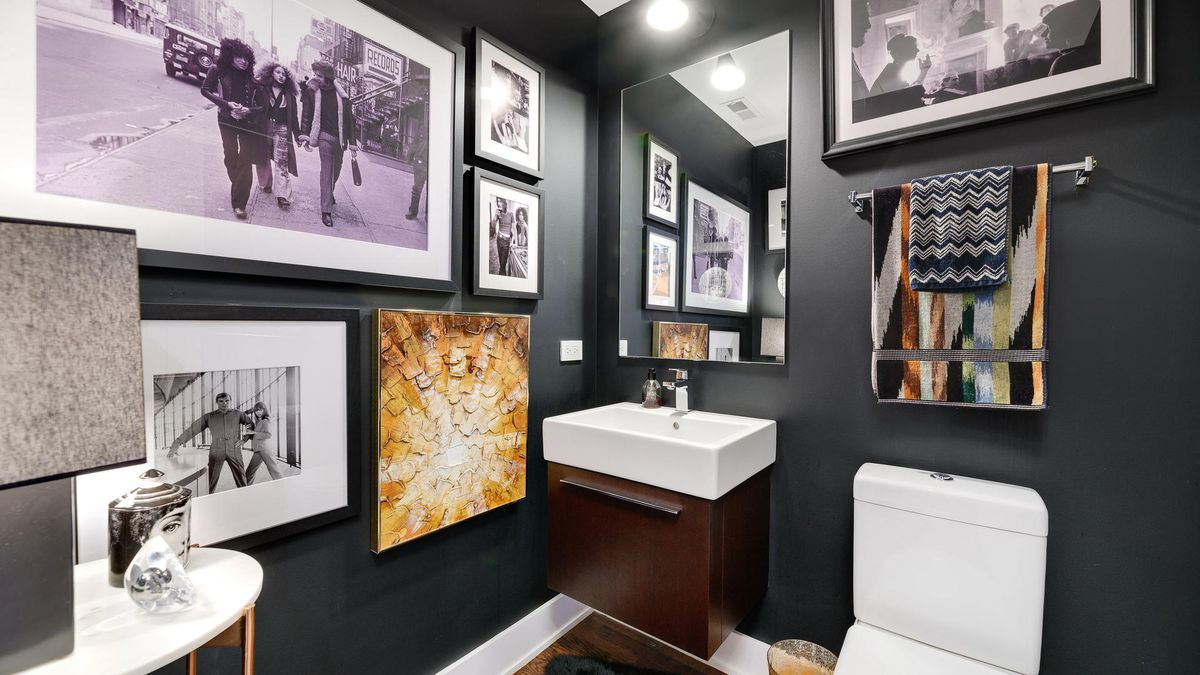 A bathroom with many framed pictures on the wall next to a sink and toilet.