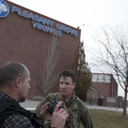 Law enforcement officials confer during a lockdown at Pleasant Grove High School on Thursday, Dec. 3, 2015. Pleasant Grove High School was placed on lockdown after receiving reports of a man with a weapon inside the school.
