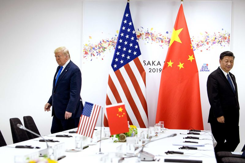 Trump and Xi on opposite sides of a table with flags in the background.