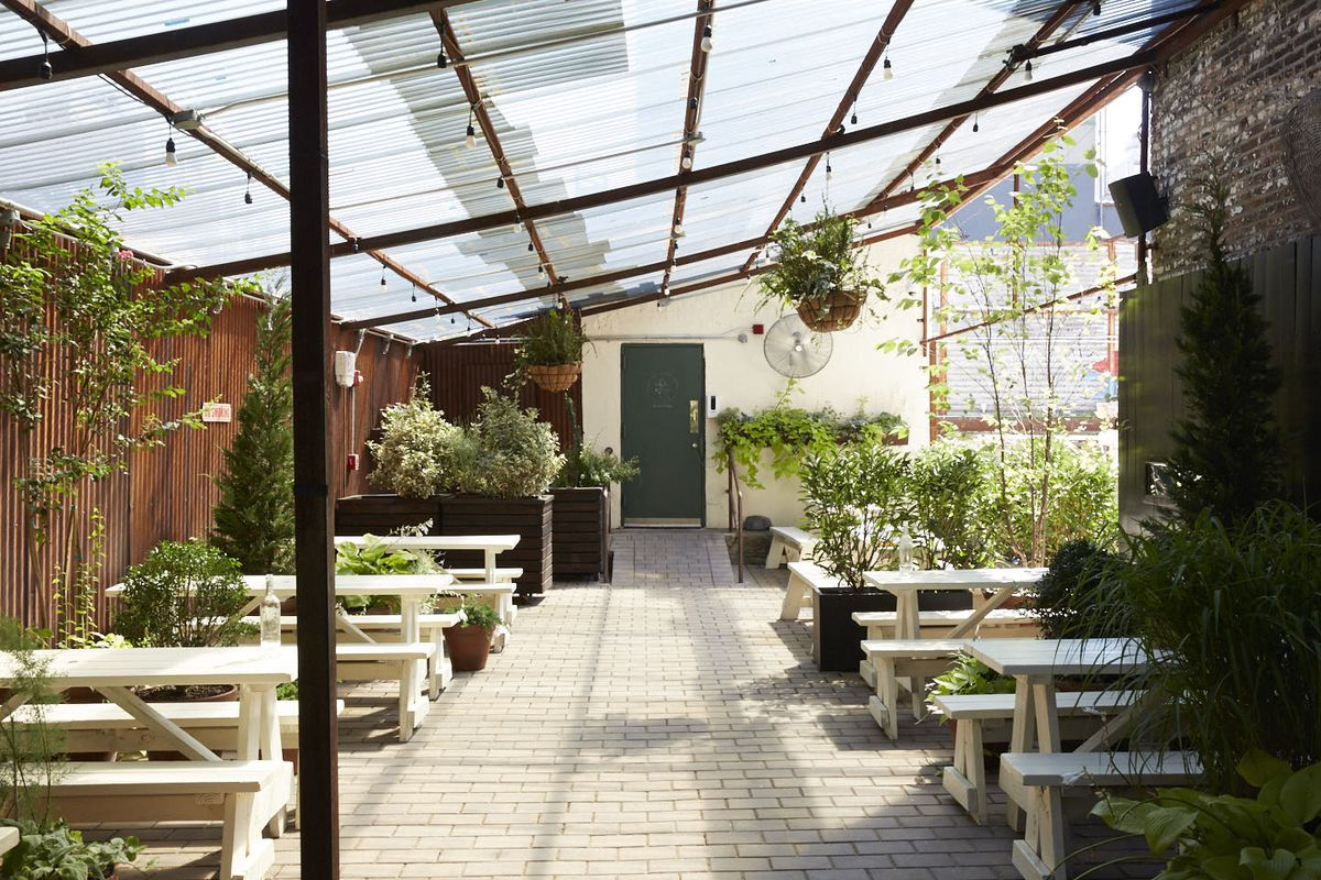 An outdoor dining area with lots of hanging potted plants and white picnic tables for eating