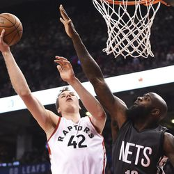 Toronto Raptors center Jakob Poeltl (42) shoots over Brooklyn Nets forward Quincy Acy (13) during the second half of an NBA basketball game Friday, Jan. 13, 2017, in Toronto. (Frank Gunn/The Canadian Press via AP)