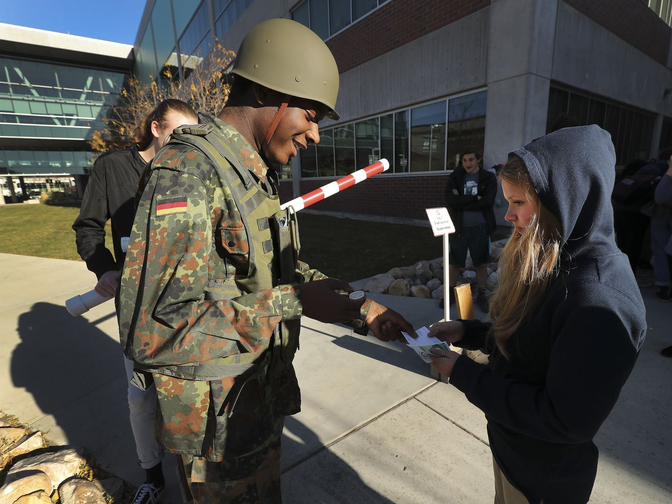 Tariq Petrus checks Anna Petersen's credentials at a a checkpoint as high school students from across the state celebrate the 30th anniversary of the fall of the Berlin Wall at Utah Valley University in Orem on Friday, Nov. 8, 2019. Students celebrated by creating graffiti on a giant replica of the wall, dancing to East German disco music and looking over German memorabilia.