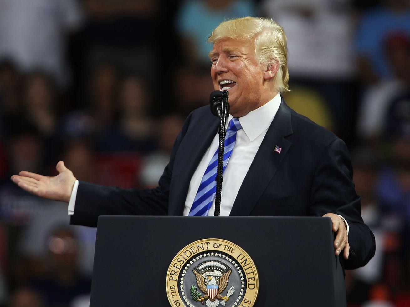 Donald Trump standing at a podium.