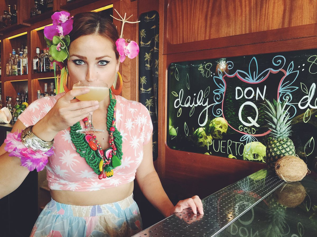 A bartender in a tiki bar wearing tropical clothes, sipping a drink