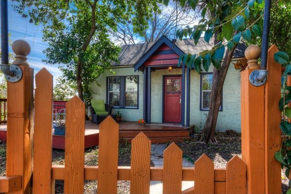 close-up of cedar picket fence with small 1930s frame home behind it, small red deck in front