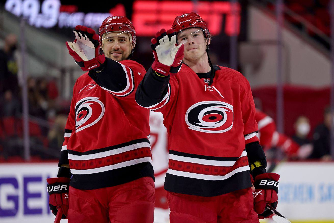 Nino Niederreiter #21 of the Carolina Hurricanes and teammate Andrei Svechnikov #37 acknowledge a fan on the glass during an NHL game against the Detroit Red Wings on April 29, 2021 at PNC Arena in Raleigh, North Carolina.
