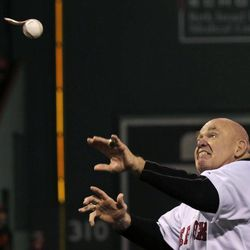 """Former professional wrestler George """"The Animal"""" Steele watches as the baseball unravels while throwing out the ceremonial first pitch prior to a baseball game against the Baltimore Orioles at Fenway Park in Boston, Friday, Sept. 21, 2012."""