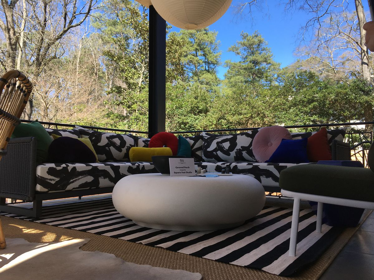 A whimsical couch on a porch with trees beyond.