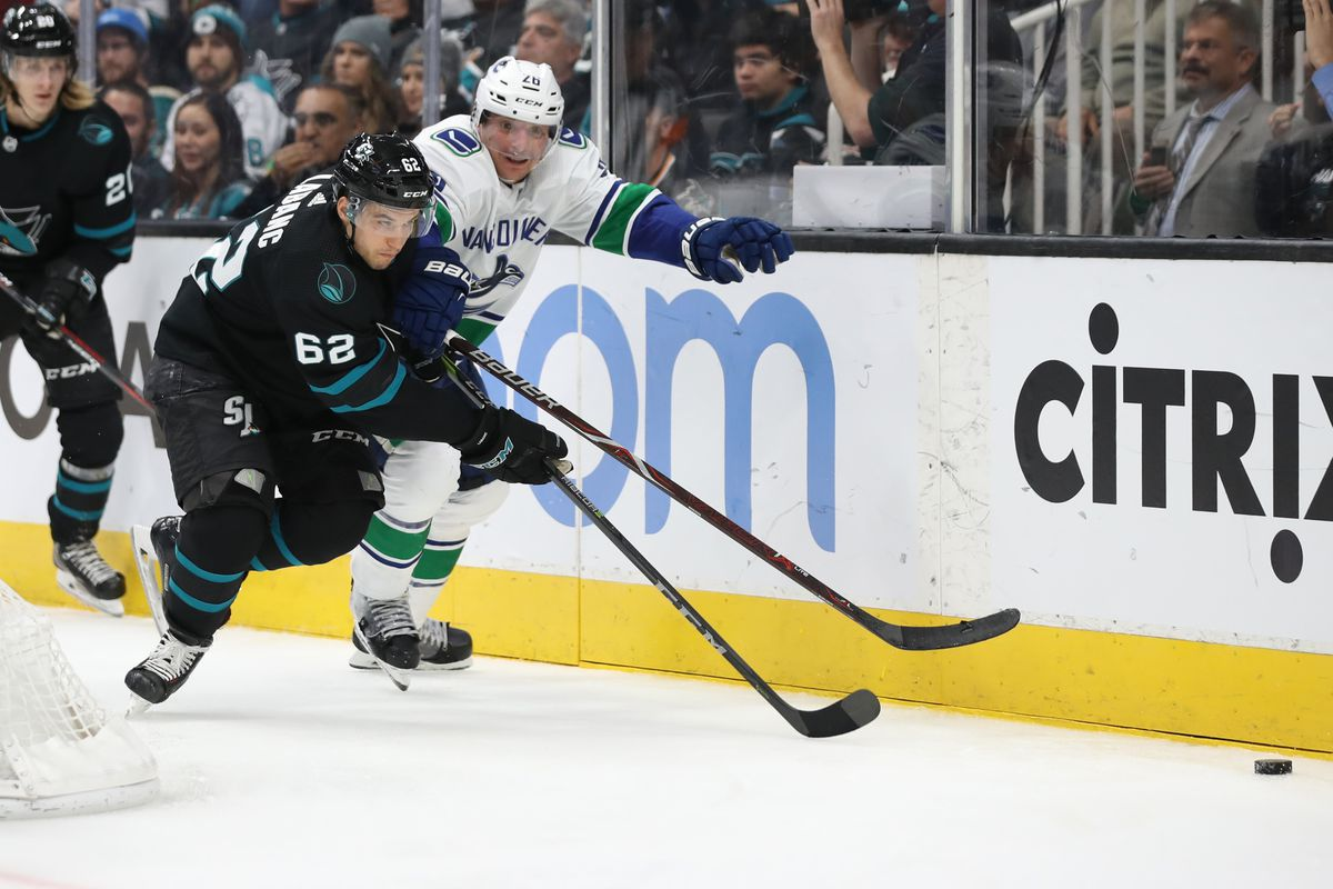 Nov 23, 2018; San Jose, CA, USA; San Jose Sharks right wing Kevin Labanc (62) and Vancouver Canucks left wing Antoine Roussel (26) chase after the puck during the second period at SAP Center at San Jose.