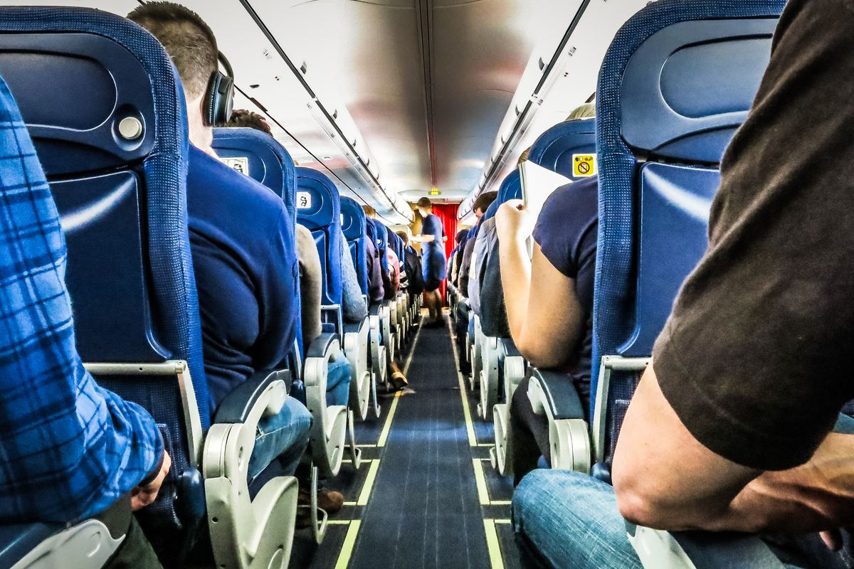 The interior of a passenger plane aisle with people in the seats to either side.