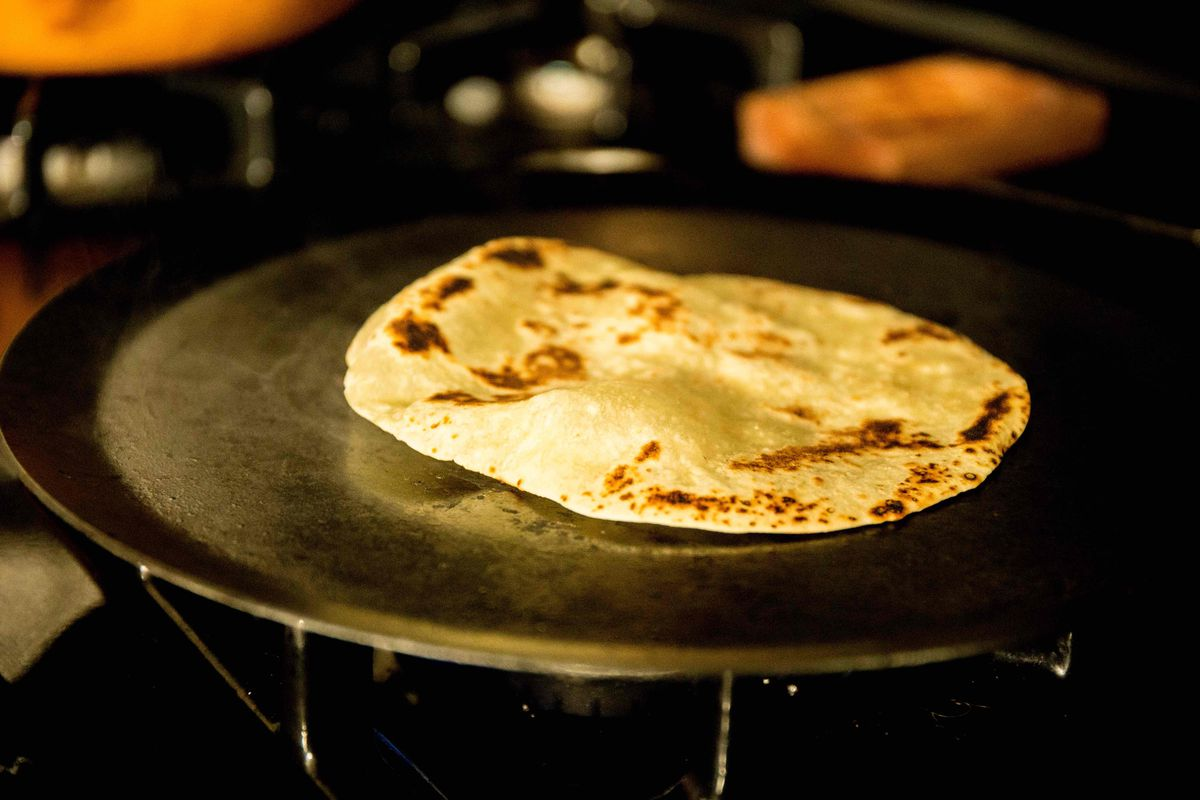 A flour tortilla, blistered in spots, puffs up on the griddle