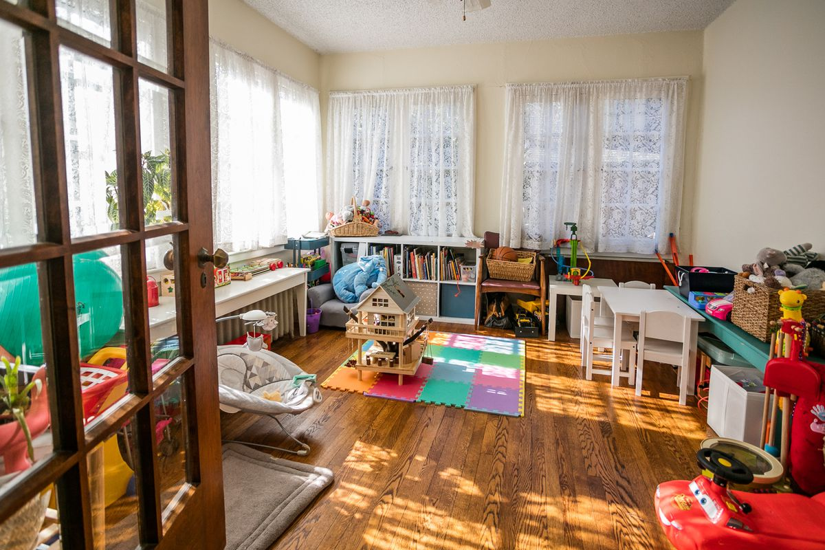 A sunny first floor room with hardwood floors that's been turned into a kids play area. There's all kinds of toys and short shelves with childrens' books.