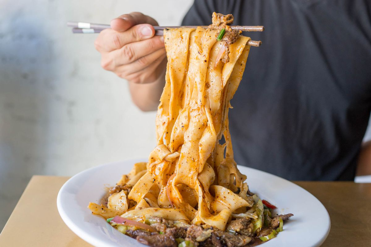 Xi'an Famous Foods' spicy cumin lamb noodles sit on a white plate as a person pulls them up