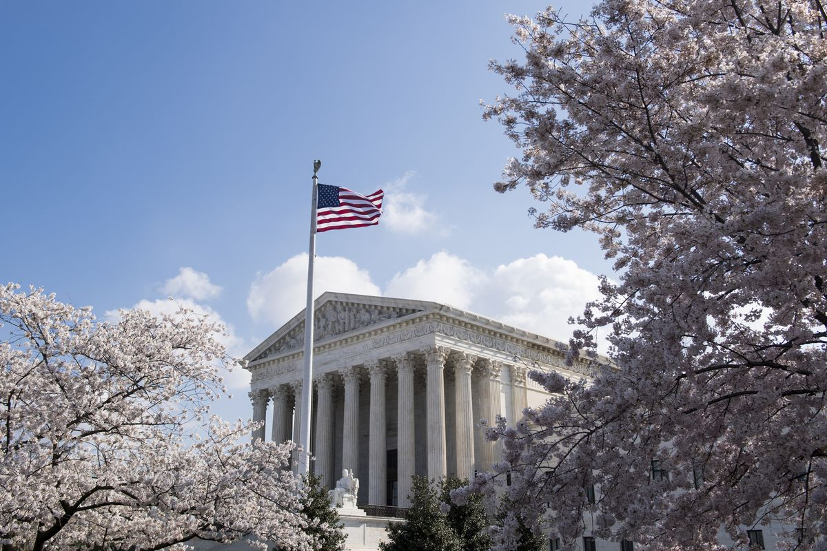 The Supreme Court building in Washington, D.C., with a flag on a flagpole and framed by blossoming cherry trees