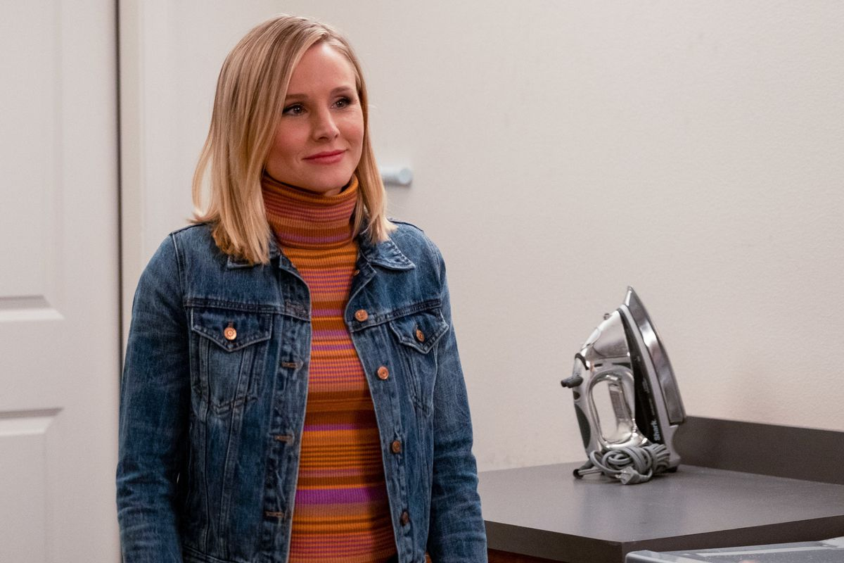 Eleanor standing next to an iron and wearing a denim jacket over a striped orange and pink turtleneck