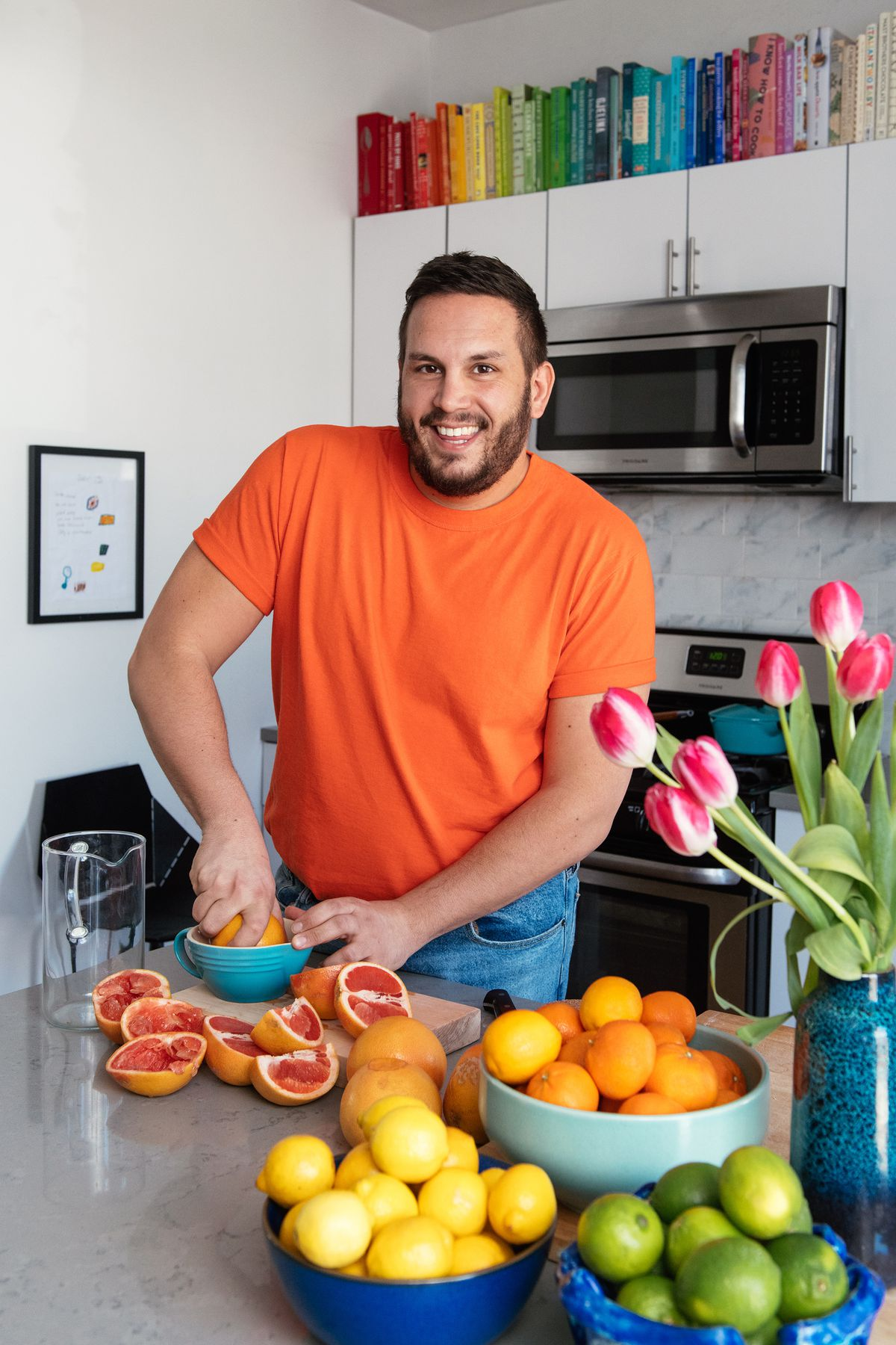 A man smiles at the camera while standing in the kitchen juicing a grapefruit. There are many grapefruits on the counter in front of him. In the background are various kitchen appliances.